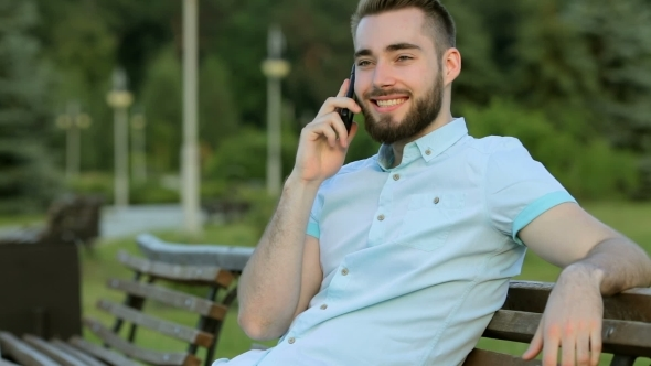 VideoHive Smiling Handsome Man Talking On The Phone In Park 12221298