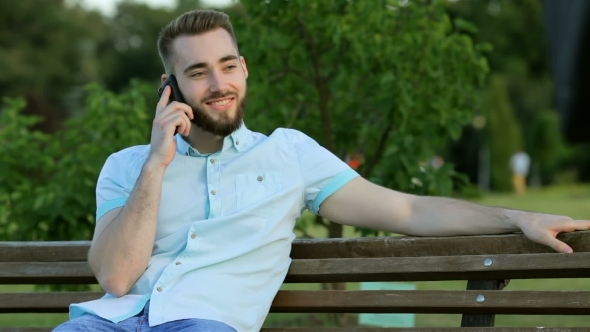 VideoHive Smiling Handsome Man Talking On The Phone In Park 12221305