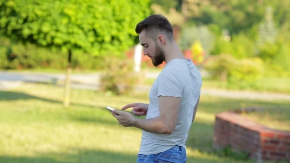 VideoHive Young Man Standing In The Park With Mobile Phone 12221338