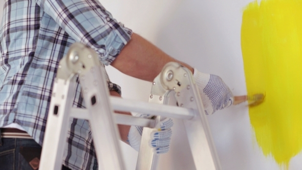 VideoHive Male Hands In Gloves Painting Wall With Paintbrush 12239083