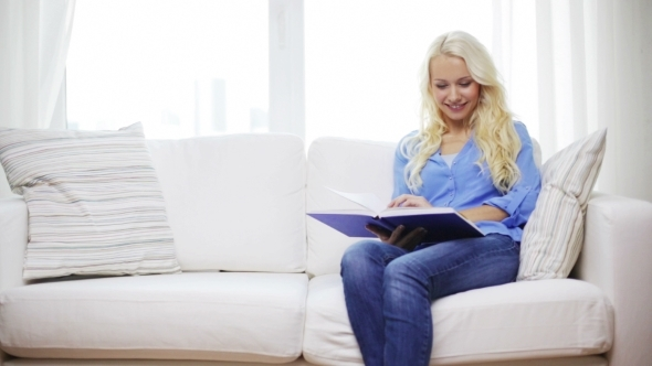 VideoHive Smiling Woman Reading Book And Sitting On Couch 12239231
