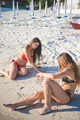 two beautiful young women lying in the sand at the beach