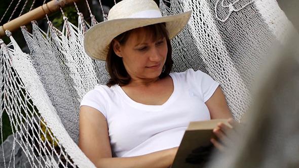 VideoHive Happy Woman Reading Book In Hammock 12276290