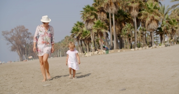 VideoHive Mother Walking On a Beach With Her Small Daughter 12279869