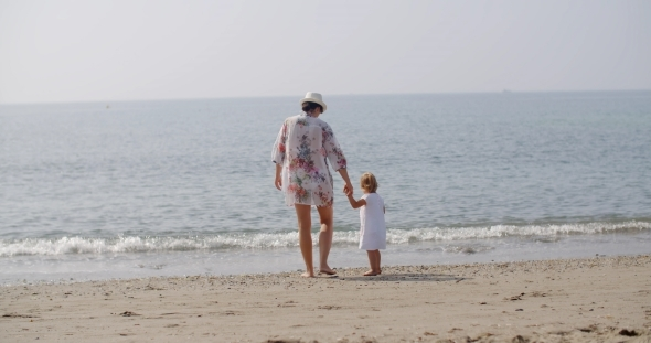 VideoHive Woman Walking Hand In Hand With Child On Beach 12279917