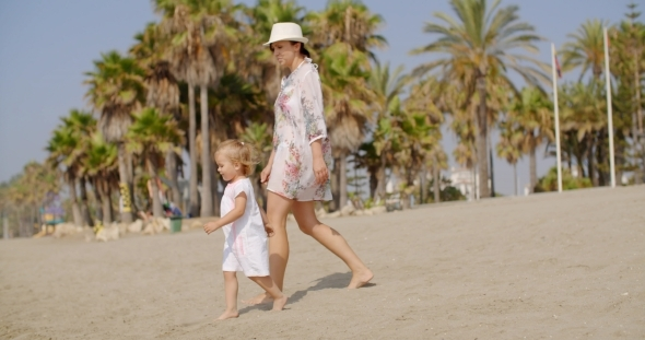 VideoHive Mother Walking On a Beach With Her Small Daughter 12279930