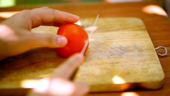 VideoHive Female Hands Sliced Tomato On a Wooden Board 12280044
