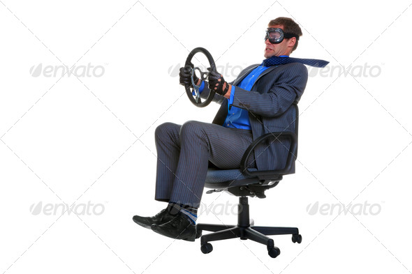 Businessman driving an office chair - Stock Photo - Images