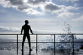 Silhouette of young man standing at the seaside, wave splash - PhotoDune Item for Sale