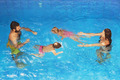 Children with parents swimming underwater in blue pool