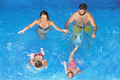 Happy family with children swimming with fun in blue pool