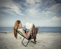 Young woman reading a book at the seaside