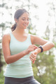 Happy jogger looking at watch in the nature