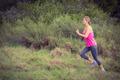 Pretty blonde athlete jogging in the nature