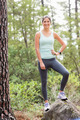 Happy jogger looking at camera in the nature