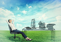businesswoman relaxing at her desk in the middle of a green meadow