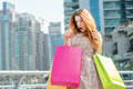 Surprised shopaholic. Young girl holding shopping bags and surpr