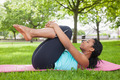 Young woman doing pilates on mat in the park