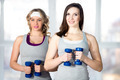 Two sporty young females doing side bends with dumbbells