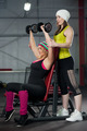 Coach assists to female in training with dumbbells in gym