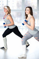 Two sporty young women doing aerobics with dumbbells