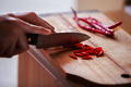 Hand slicing chilli pepper  on wooden background.