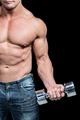Midsection of bodybuilder exercising lifting dumbbells against black background