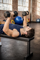 Man lifting dumbbells lying on exercise bench at the gym