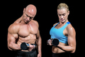Muscular man and woman concentrating while lifting dumbbells against black background