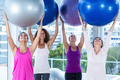 Cheerful women holding exercise balls with arms raised in fitness studio