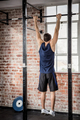 Rear view of man doing pull ups at the gym