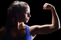 Confident female athlete flexing muscles against black background