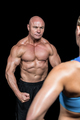 Bodybuilder flexing muscles in front of instructor against black background