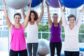Portrait of cheerful women holding exercise balls with arms raised in fitness studio