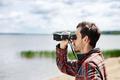 Man looks through binoculars while fishing at the lake on vacati
