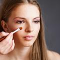 girl applying make-up by make-up artist.