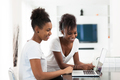African American student girls using a laptop computer - black p