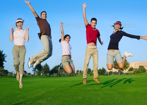 group of young people jumping outdoors grass - Stock Photo - Images