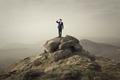Businessman standing on a rock