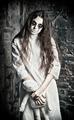 Horror scene: strange mysterious girl with moppet doll in hands