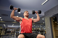 young man with dumbbells flexing muscles in gym