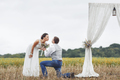 Proposal moment on happy wedding day of young newlywed couple.
