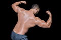 Bodybuilder man flexing his muscles against black background