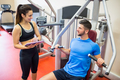 Trainer working with athlete at weights machine at the gym