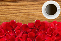 beautiful red rose petals and coffee cup over wood texture close