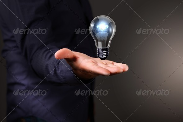 Human hand holding electric bulb - Stock Photo - Images