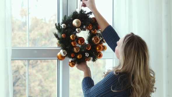 Girl Hangs a Christmas Wreath On a Window