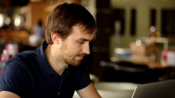 VideoHive a Man Sitting In a Cafe And Working At a Laptop 13525615