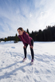 yougn woman jogging outdoor on snow in forest