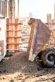 Dumper truck unloading construction gravel, granite and crushed stones at building foundation